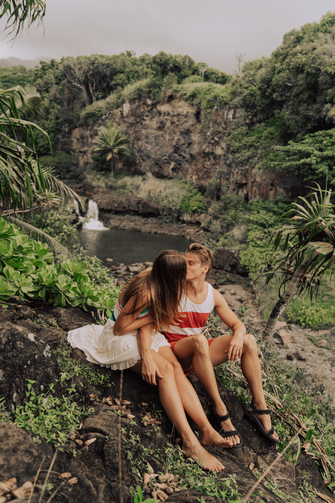 man and women kissing with a waterfall and palm trees in the background.