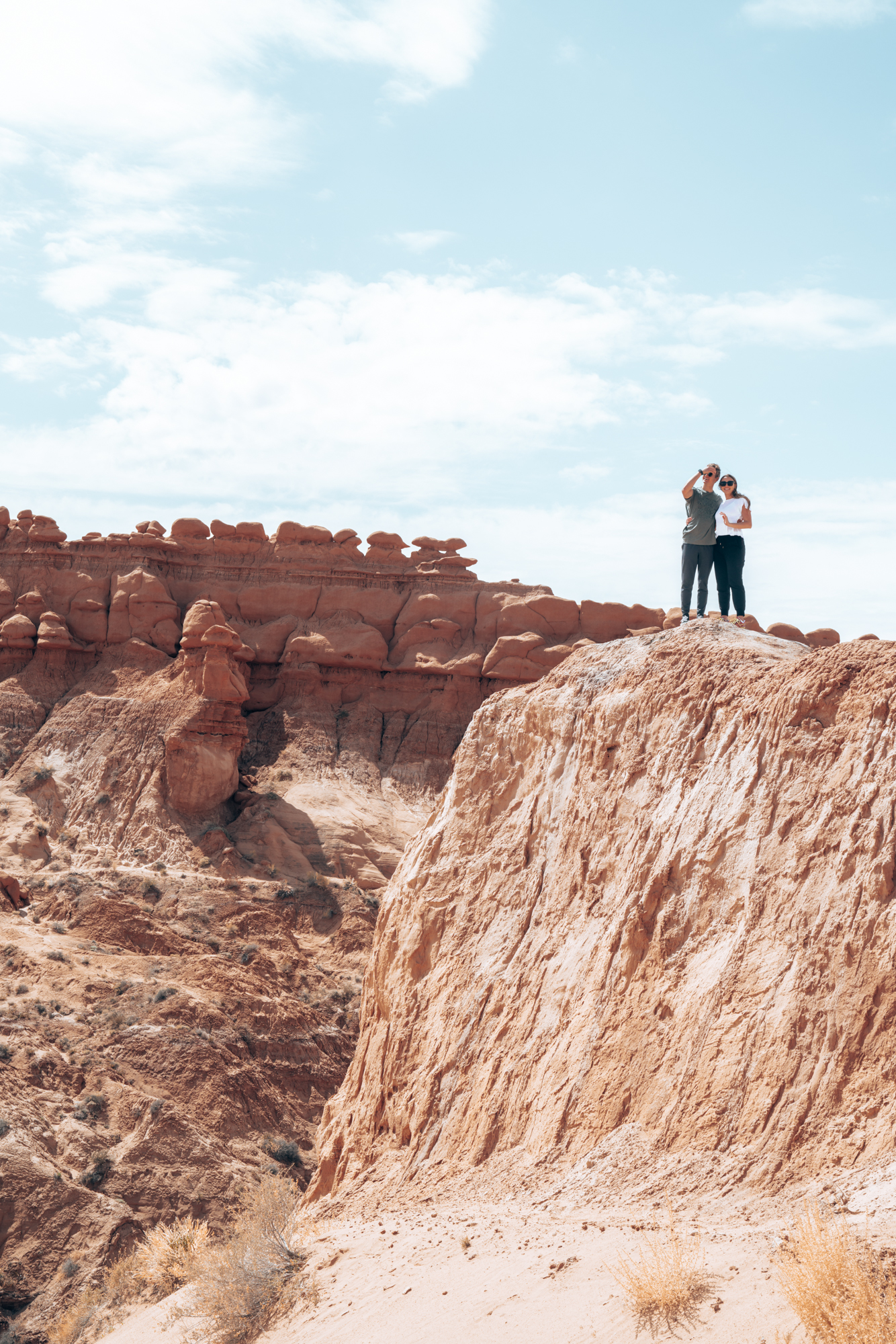 a young couple pose at the edge of cliff with red rock and blue skies behind them.