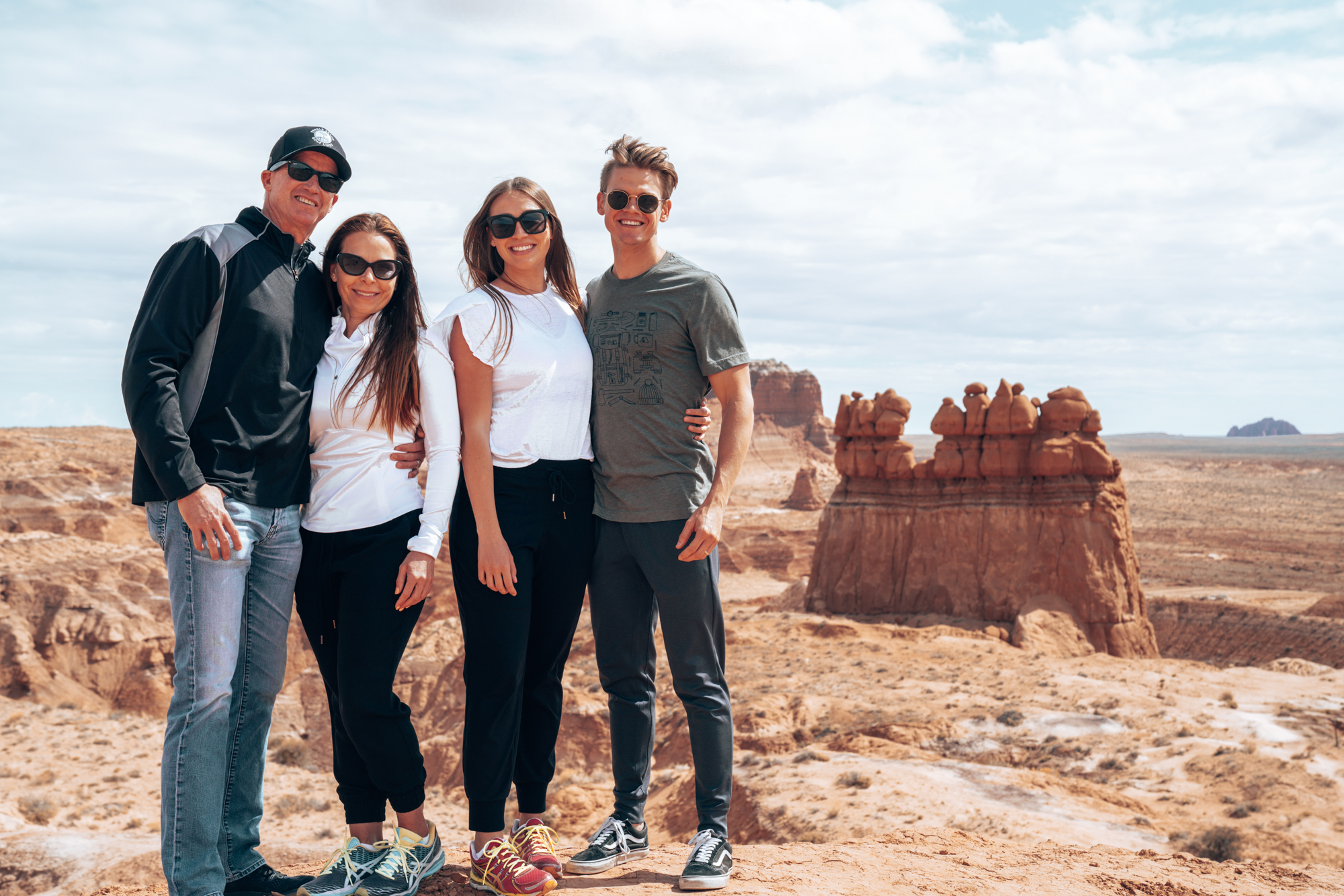a family of four pose in on a cliff with red rock buttes and blue skies behind them.