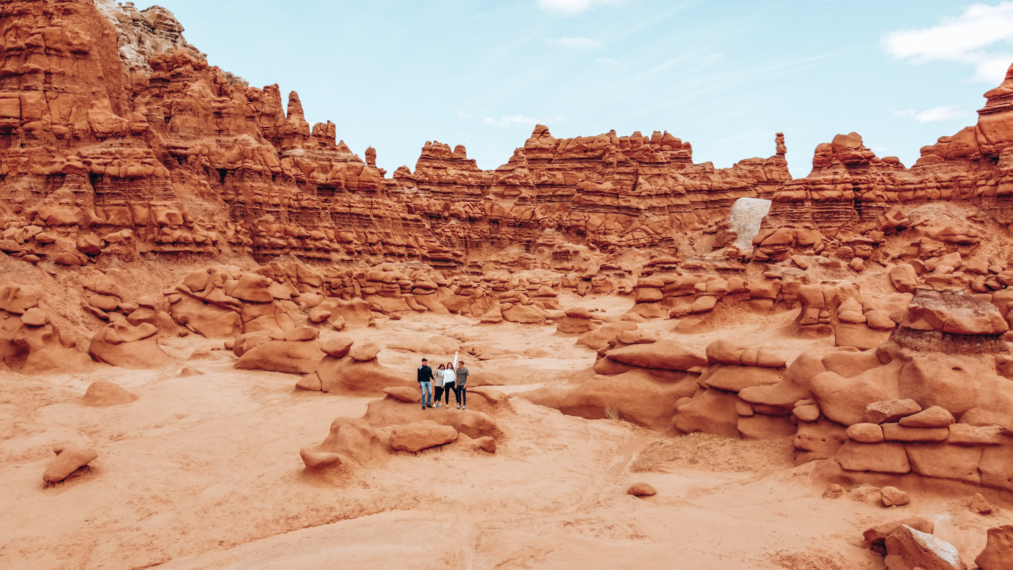 Four people can be seen in the foreground of an image with red rocks and cliffs!