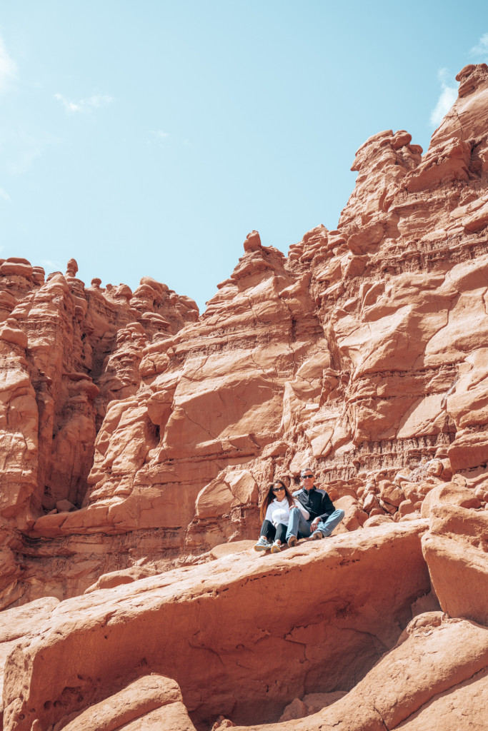 A man and a women sit on a large red rock in Southern Utah.