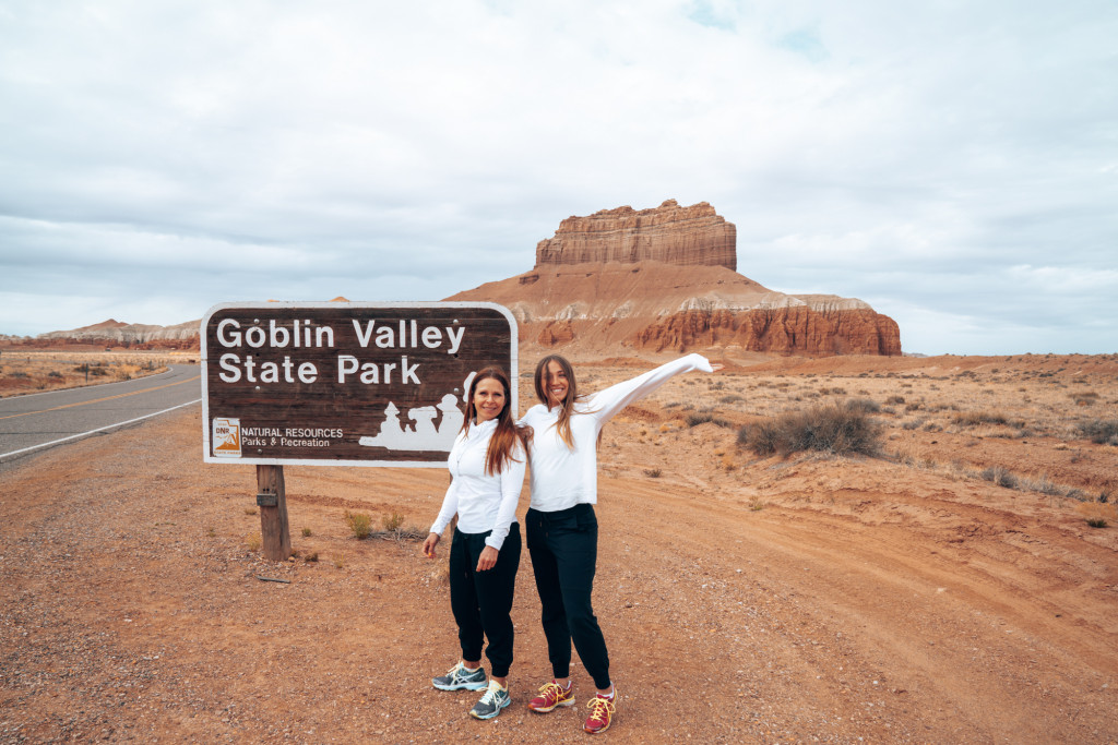 Two women standing in front of the Goblin Valley State Park with arms up.