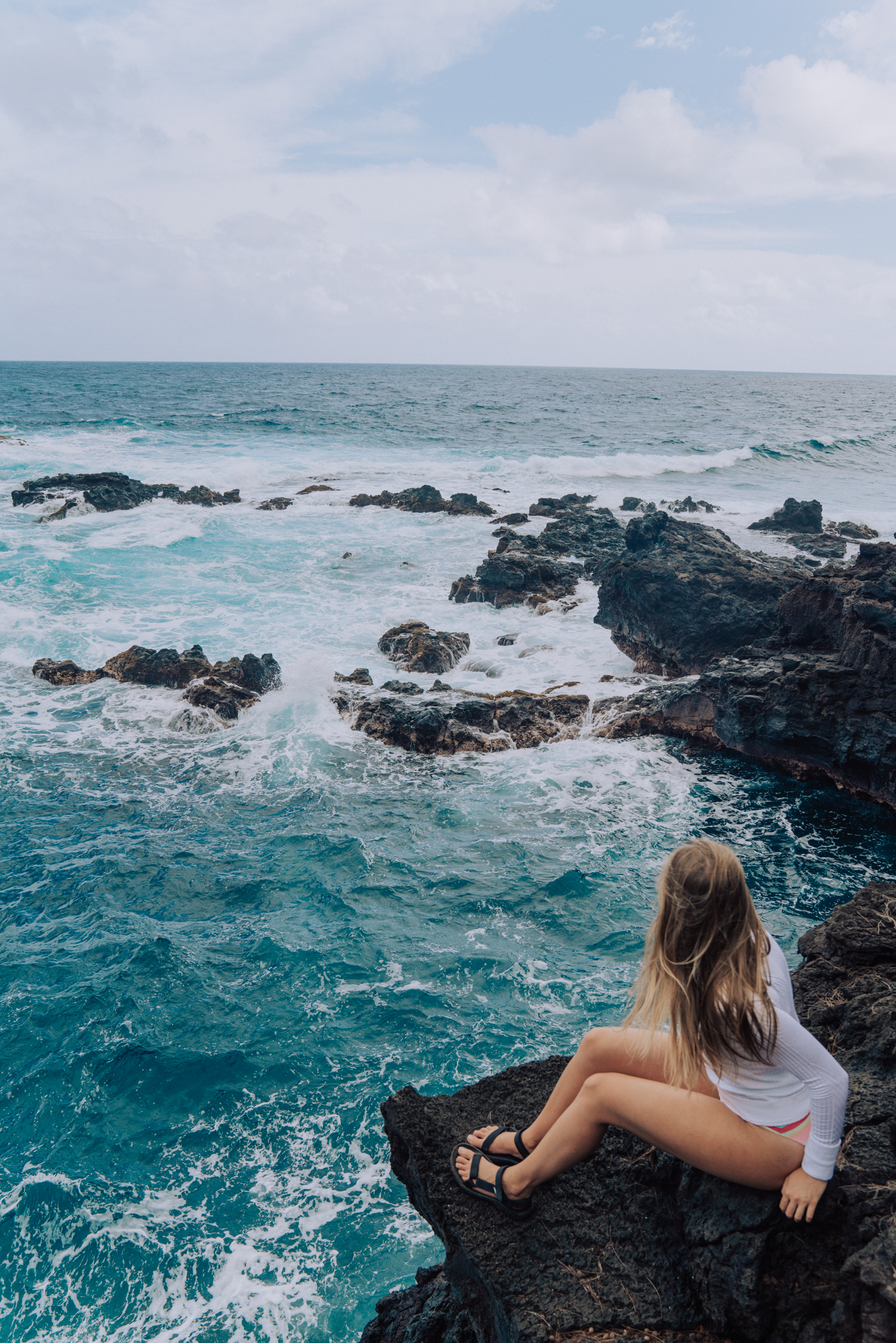 woman overlooking the ocean below from a cliff.