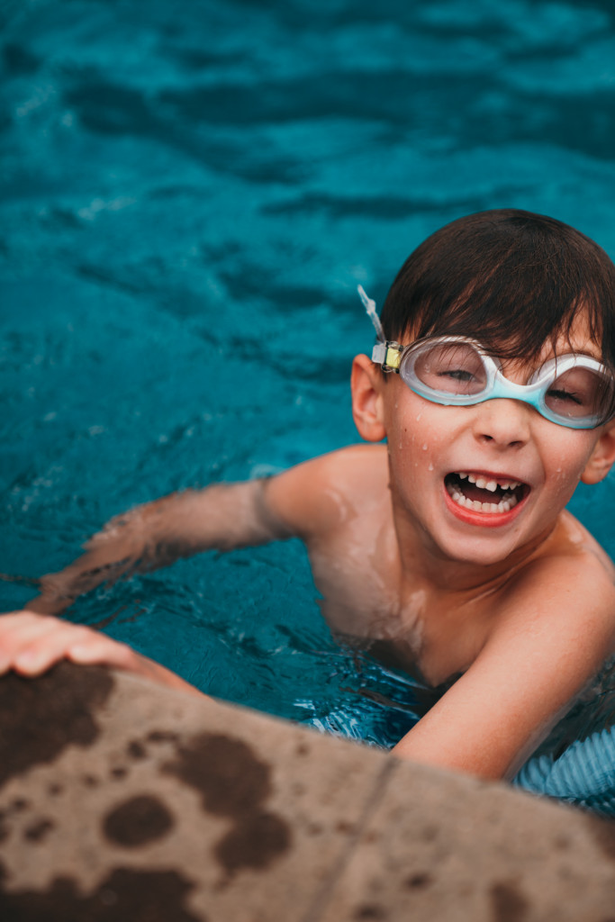 A little boy swims in a backyard swimming pool.