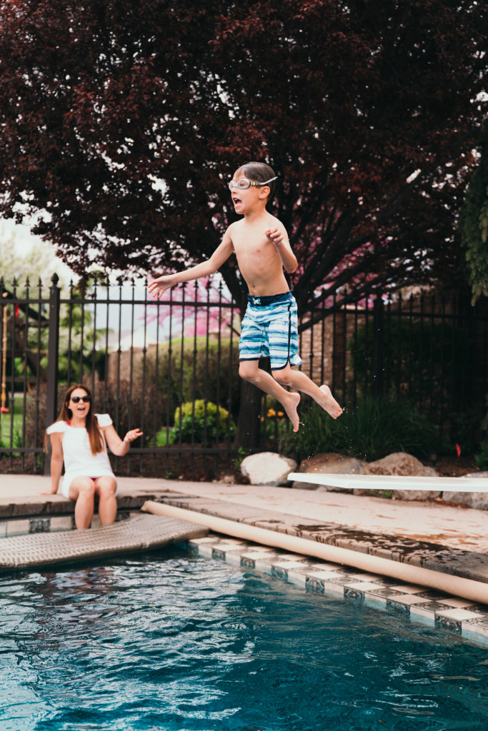 A little boy jumps off a diving board in a backyard swimming pool.