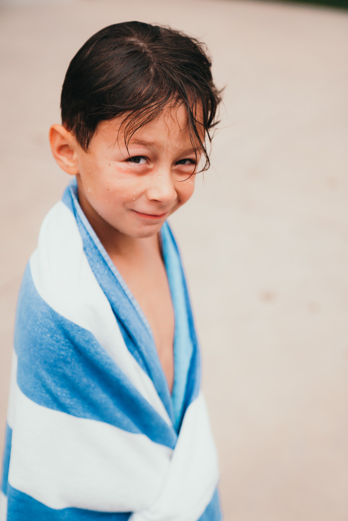 A little boy is wrapped up in a blue and white pool towel.