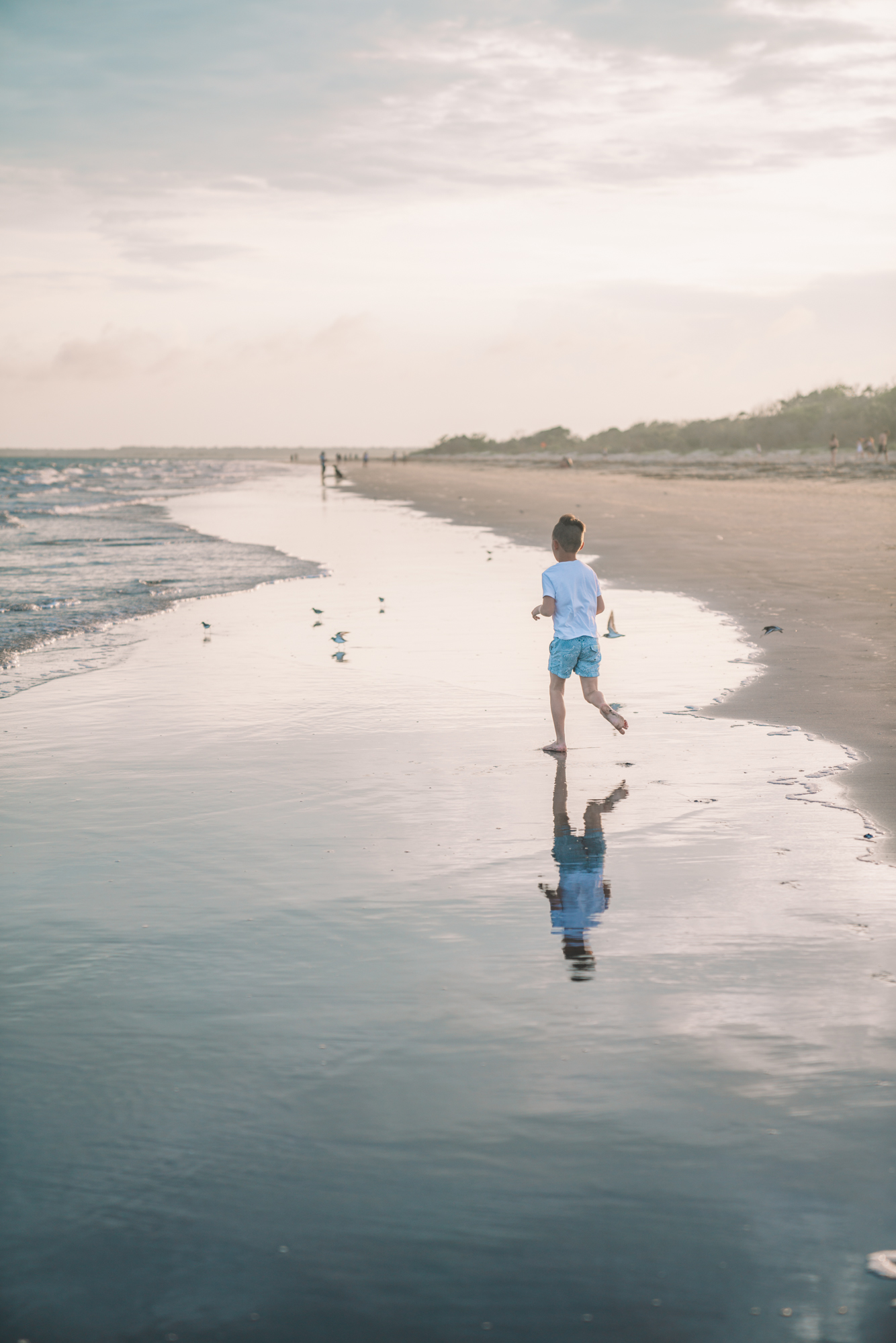 Things to do in Charleston sc with kids - A little boy runs along the shore on the beach - his reflection can be seen in the water.