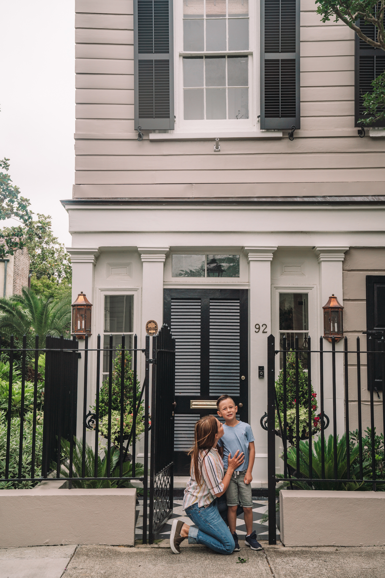 charleston sc visitors guide - a little boy and his grandma smile in front of a grand southern home.