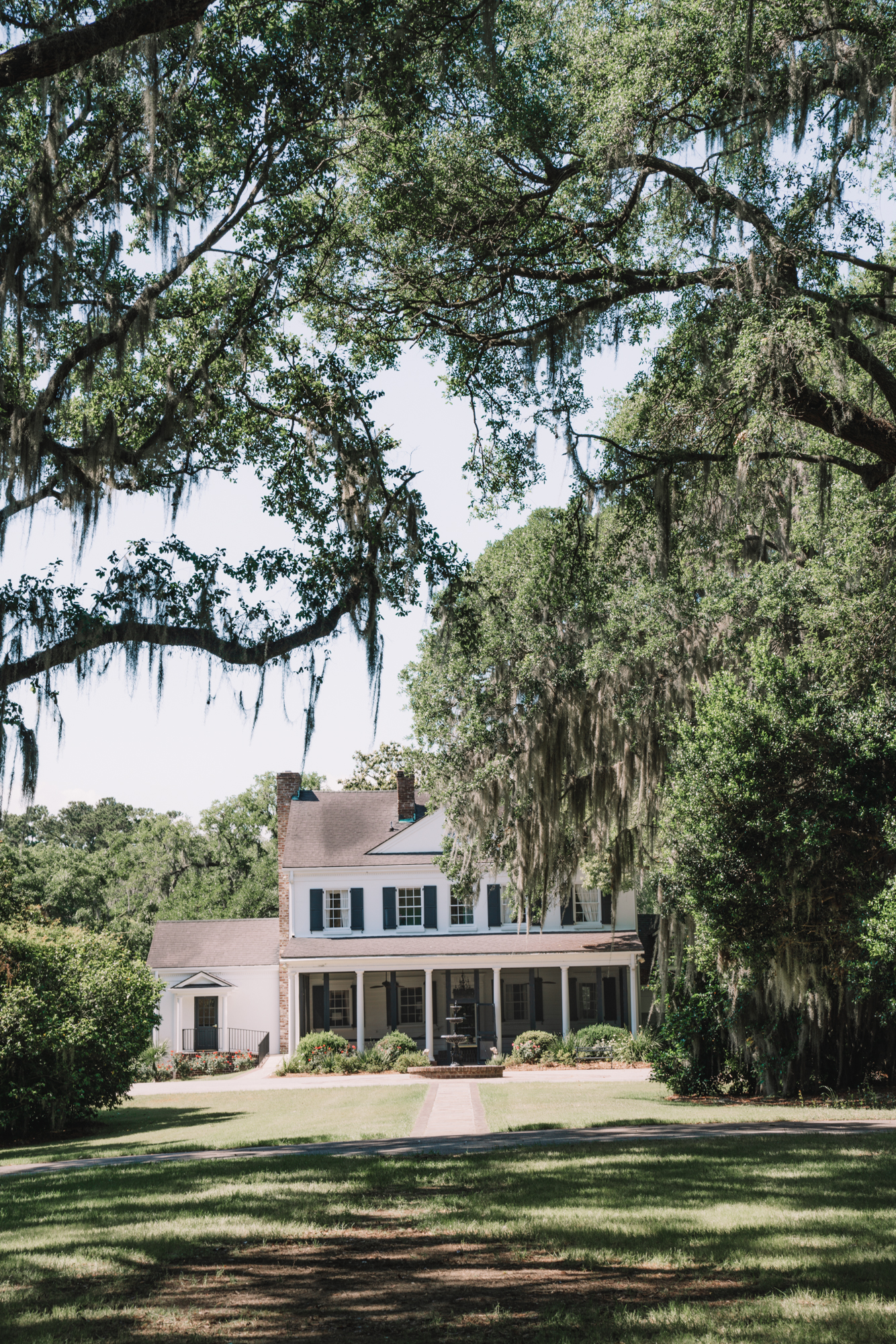 Things to do in Charleston sc with kids - a white plantation house with black shutters stands beneath oak trees hanging Spanish moss.