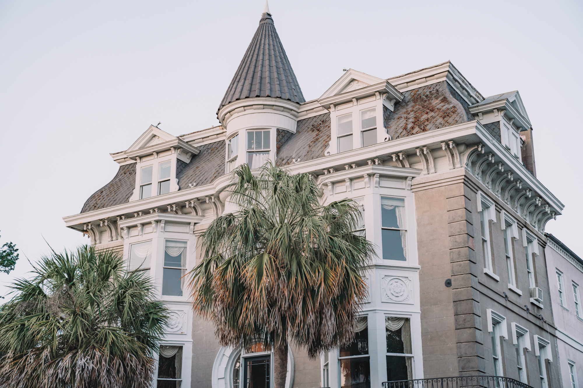 charleston sc visitors guide - a giant antebellum house with palmetto trees in front.