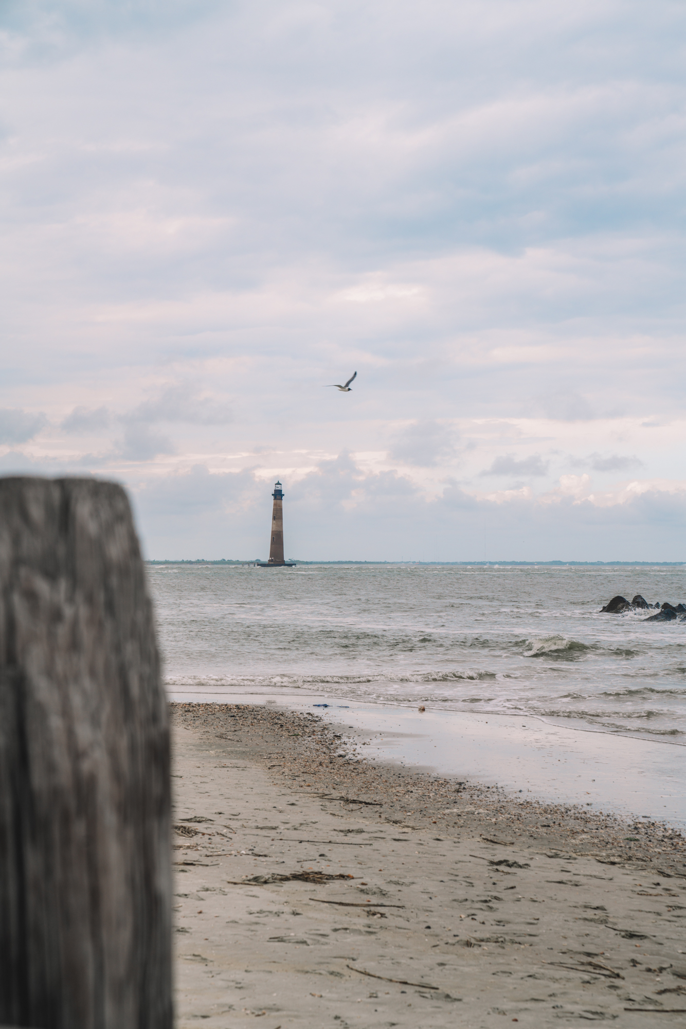 A red and white lighthouse stands far away with the beach in the foreground.