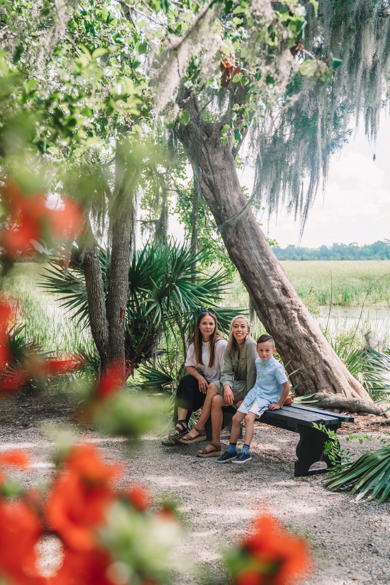 Things to do in Charleston sc with kids - a family sitting on a bench with tupelo trees with spanish moss hanging.