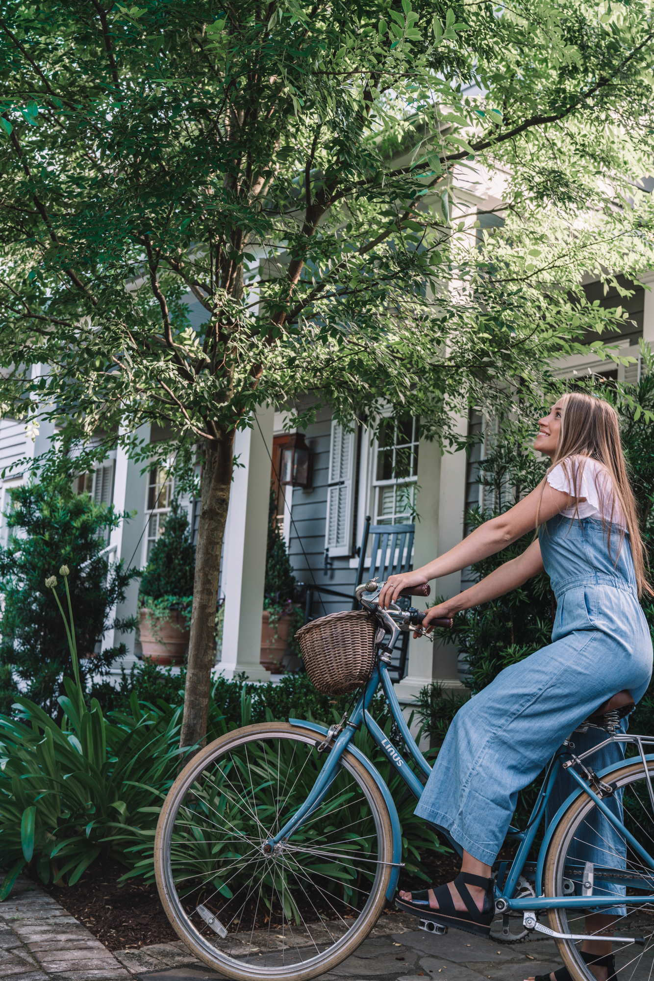 charleston sc visitors guide - a women sits on a blue bike in front of a blue southern home.
