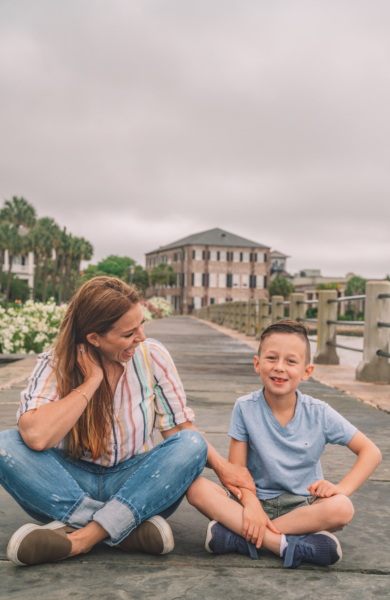 Things to do in Charleston sc with kids - a young boy and his grandma play on the sidewalk with antebellum style houses in the background.