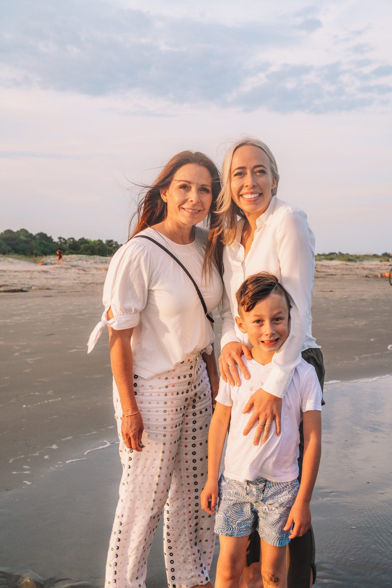 a small family smiles on the shore of the beach during sunset.