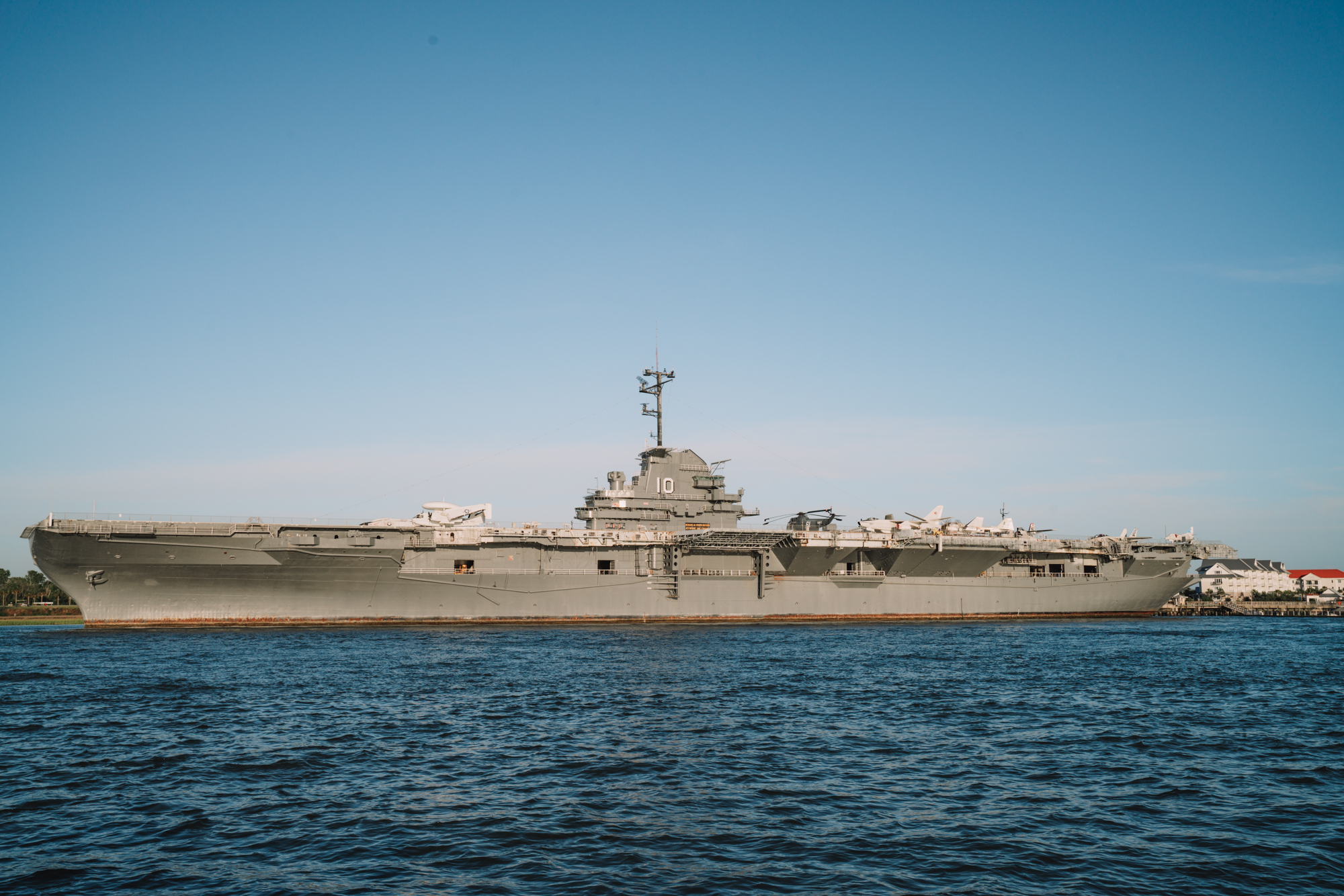 A gray naval ship sits on the water