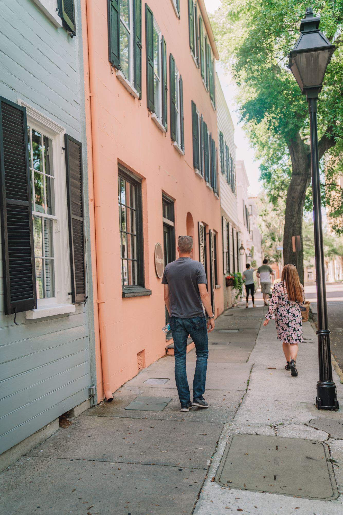 charleston sc visitors guide - a man and a women walk in front of the brightly colored souther houses in Charleston
