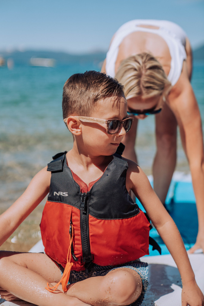 a little boy sits on the front of a paddle board with a life jacket on
